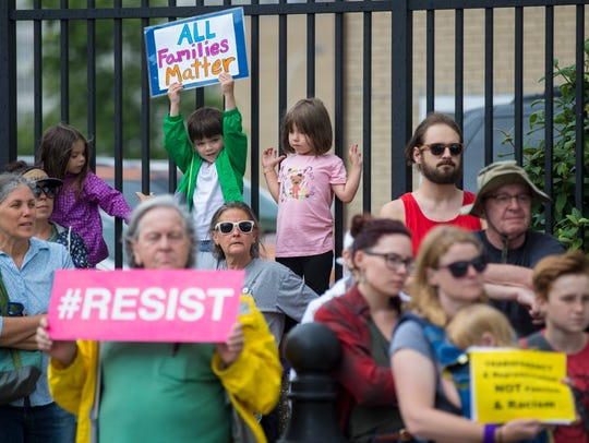 Protesters hold signs across from the U.S. Immigration