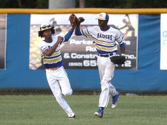 Rickards' Malik Magwood, left, high-fives Rohan Wright after a catch in the out field against South Walton during their Region 1-5A semifinal game at the Rickards Sports Complex on Tuesday, May 8, 2018.