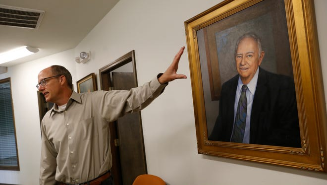 John Byrom, outgoing CEO and president for D.J. Simmons, talks about A.B. Geren on July 1 in front of Geren's portrait at D.J. Simmons' offices in Farmington.