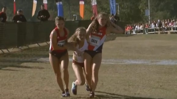Runners from Clemson and Louisville help a fallen opponent