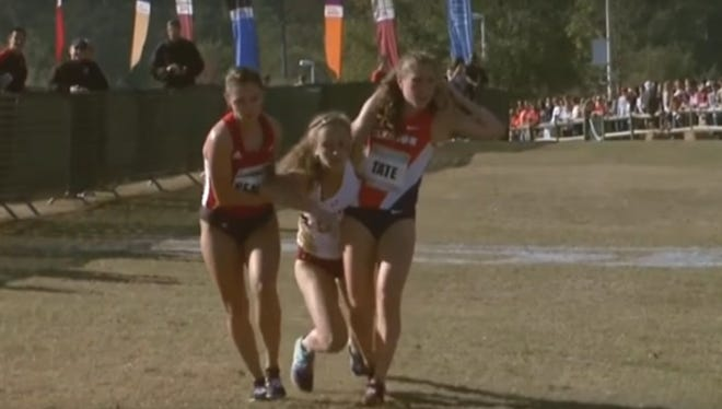 Runners from Clemson and Louisville help a fallen opponent from Boston College cross the finish line during the 2016 ACC Cross Country Championships.