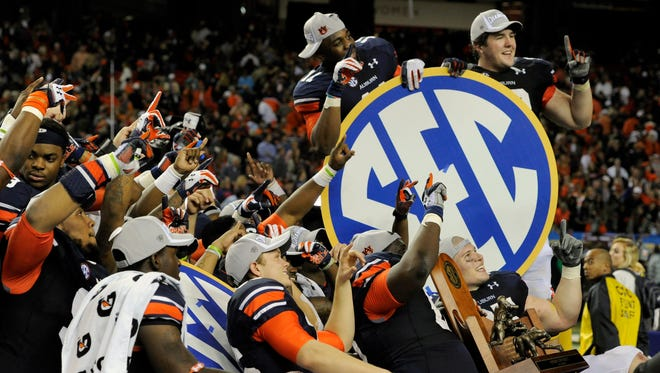 The Auburn Tigers celebrate with the trophy after defeating the Missouri Tigers in the 2013 SEC Championship Game at Georgia Dome. Auburn won 59-42.