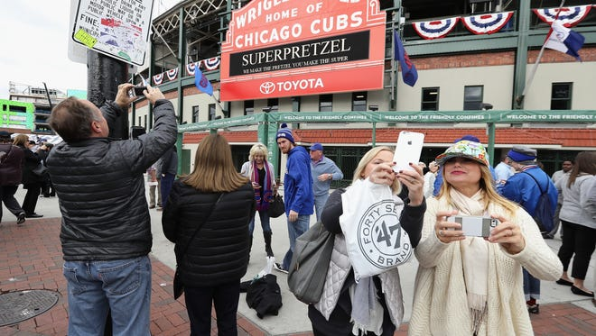 Fans take photographs outside of Wrigley Field on Thursday, a day before the Chicago Cubs are set to host the Cleveland Indians in Game 3 of the 2016 World Series.
