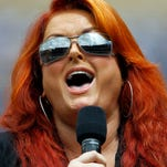 Country music singer Wynonna Judd sings the National Anthem prior to a baseball game between the Los Angeles Dodgers and the Chicago Cubs on Sunday, Aug. 3, 2014, in Los Angeles.