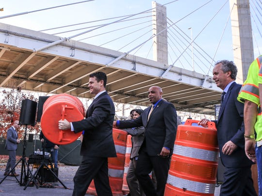 Indiana Senator-elect Todd Young carries an orange traffic barrel as Louisville Mayor Greg Fischer follows after the official celebration of the completion of the downtown crossing portion of the Ohio River Bridges Project Friday afternoon.