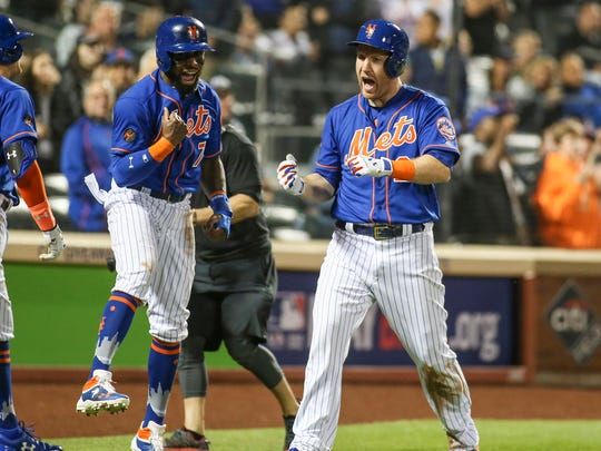 New York Mets third baseman Todd Frazier (21) is congratulated by second baseman Jose Reyes (7) after hitting a two run home run in the fifth inning against the New York Yankees at Citi Field.