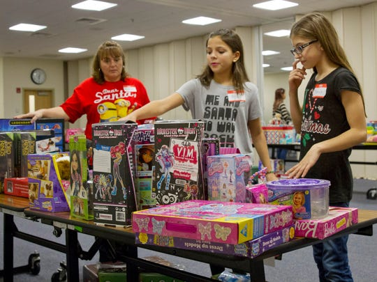 Heather Tatur, Brianna Otto, 11, and Mikayla Rua, 11, all of Stafford, pick out toys from age and gender specific tables as children visit with Santa. Christmas Day dinner and party at St. Mary's Church in Stafford with a visit by Santa with presents for the children.
