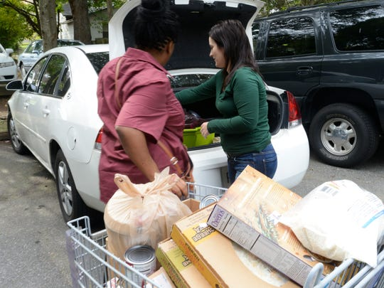 ABCCM Counselor Mary Wood, right, loads food into the trunk of a woman's car on Monday, Sept. 21, 2015. The mother of four is a full-time manager at McDonald's but says she does not make enough to feed her family.