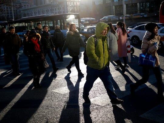 People walk past motorists stuck on a traffic jam during