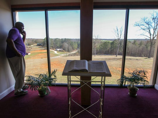 Minister Edgar Scott, church administrator, looks out a bay window in the prayer room at Generostee Baptist Church, overlooking countryside in Starr.