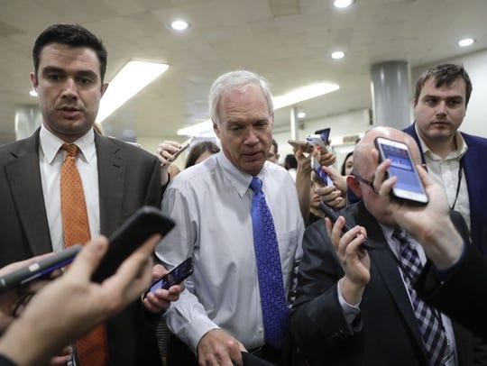 Sen. Ron Johnson makes his way through a crush of reporters