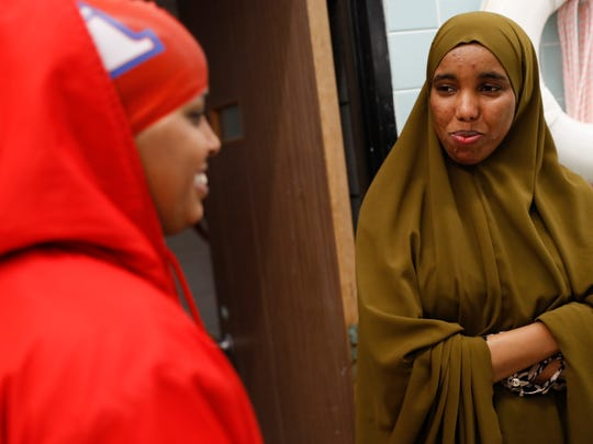In a Thursday, Oct. 5 photo, Nimo Gohe, right, chats with Suhan Mohamed before a swim meet at Apollo High School. Gohe was not swimming in this meet but cheered on her teammates. Nimo Gohe and Suhan Mohamed just learned to swim this summer and are now on the Apollo swim team.