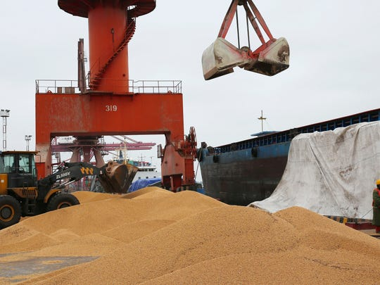 In this Wednesday, April 4, 2018 photo, workers load soybeans imported from Brazil at a port in Nantong in east China's Jiangsu province.