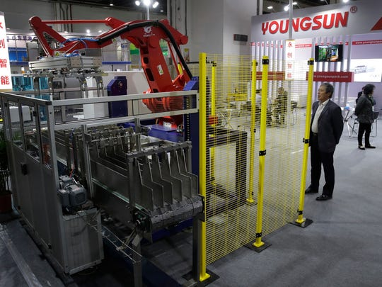 A man watches a Chinese company displaying a Chinese-made industrial robot demonstration on processing soybean at the International soybean exhibition in Shanghai, Thursday, April 12, 2018. China's government has denied President Xi Jinping's promises this week to cut import tariffs on cars and open China's markets wider were intended as an overture to settle a tariff dispute with Washington. A commerce ministry spokesman said negotiations were impossible under 'unilateral coercion' by President Donald Trump's government.