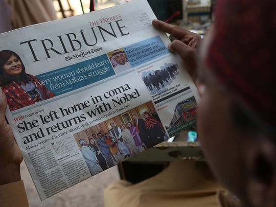 A man reads front page news of Nobel Peace Prize Laureate