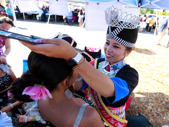 A miss Hmong pageant helps put on makeup for a dancer