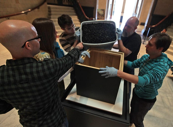 "At the Cincinnati Art Museum artist Todd Pavlisko (from left), Jeni Eckman, assistant registrar of exhibitions, and preparators P.J.Grimm, Mike Hancock and Josh Rectenwald pour used ballistic gel into a box atop a pedestal in the museum's Great Hall on Thursday, March 13, 2014. The ""Crown"" exhibition involved a sharpshooter firing through the center gallery into a large bronze cube mounted in Great Hall. The shooting was documented by multiple high-speed and regular video cameras, and that video will be part of the exhibit, with multiple monitors playing along the length of Schmidlapp Gallery."