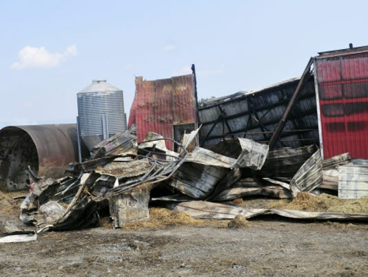 Only wreckage remained Monday of a barn that burned Sunday, along with another barn and shed at 1367 Warm Spring Road, Hamilton Township.