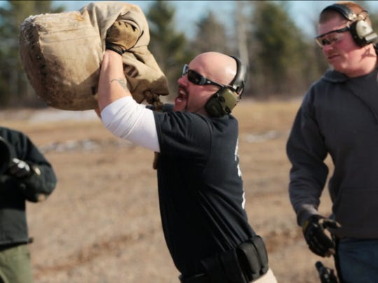 War Club President Louis Cote (center), 32 of Marquette tosses a bag of weights after doing an exercise with War Club member Damian Salmond (right) 26 of Marquette to wear themselves out before driving a truck to take aim at targets during a tactile training exercise as part of training for the War Club at a field outside of Marquette in Michigan's Upper Peninsula on Saturday November 14, 2015.