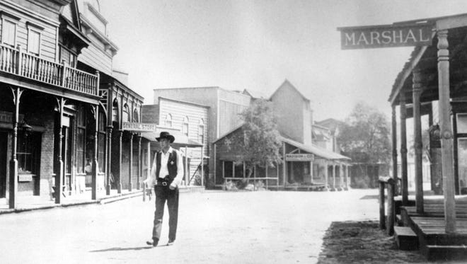 """Gary Cooper, portraying a sheriff, walks down the deserted street of the western town on a Hollywood set in the 1952 movie """"High Noon."""""""