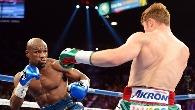 Floyd Mayweather Jr. (blue gloves) and Canelo Alvarez battle during their during their WBC and WBA super welterweight titles fight at MGM Grand Garden Arena on Saturday.