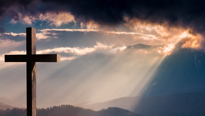 Jesus Christ cross. Christian wooden cross on a background with dramatic lighting, colorful sunset, twilight and orange -  purple clouds and sky.