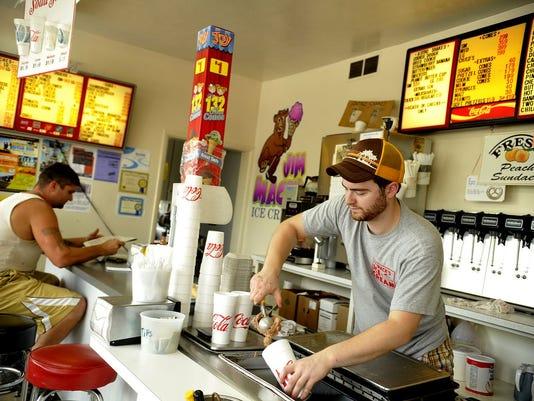 Jim Mack's Ice Cream soda jerk Jason Bartch scoops up chocolate ice cream for a milkshake.