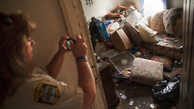 Dee Price, an animal control officer with the Waynesboro Police Department, photographs a torn-apart room in a recently condemned apartment building on the 200-block of Port Republic Road in Waynesboro on Thursday, Sept. 4, 2014.