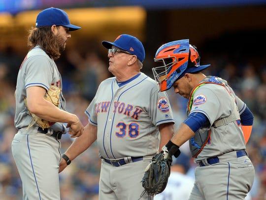 Mets starting pitcher Robert Gsellman (65) speaks with