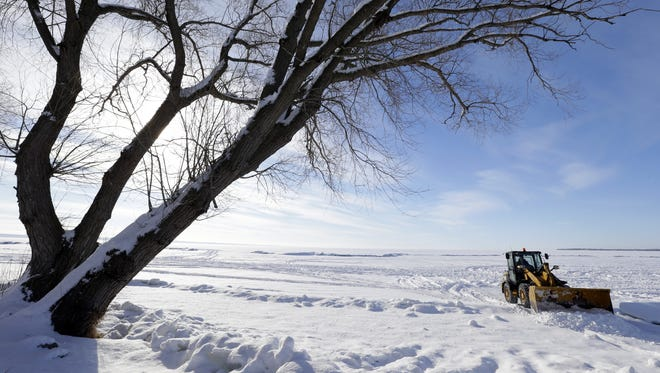 Trevor Ulman, an employee with Schmalz Custom Landscaping & Garden Center, clears snow Thursday for access to Lake Winnebago behind Waverly Beach in the Village of Harrison.