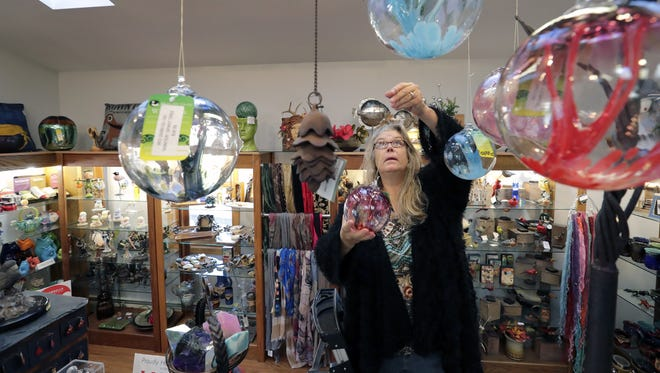 Leeann Wasinger hangs decorative art glass in The Tailored Hide Custom Leather and Repair and The Gift Gallery in Neenah.
