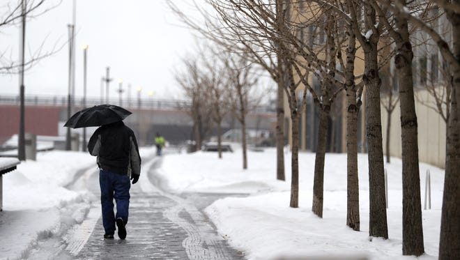 A pedestrian walks on an icy path along the Fox River in Green Bay.
