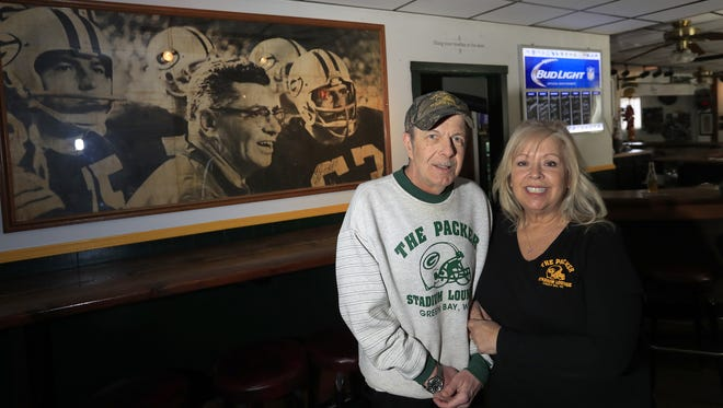 Owners Danny and Kathygail Shandor stand by a vintage Green Bay Packers photo at The Packer Stadium Lounge. Danny has owned the tavern on south Broadway since 1984. The Shandors' last day behind the bar is Tuesday. They've sold the business and will retire.