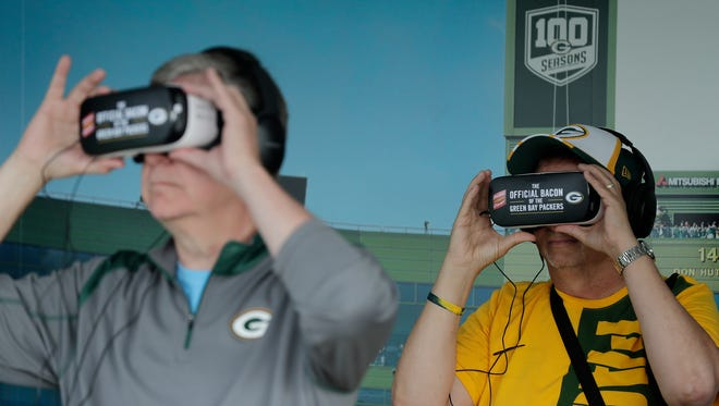 "Fans try out the ""Virtual Lambeau"" exhibit as the Green Bay Packers unveiled Lambeau Field Live, a traveling  exhibit of the Pacckers' 100 years of football, outside Lambeau Field on Tuesday."