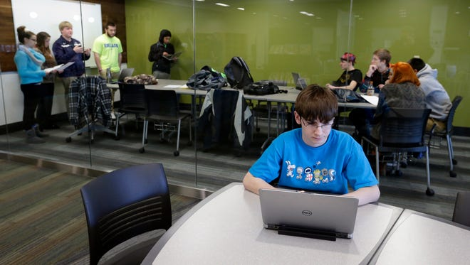 Aidan Ceszynski studies in between classes Jan. 12 in the new Learning Commons at Menasha High School. In back, a group works on an English project in the students collaborative conference room.