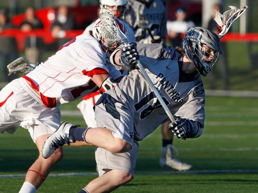 Pittsford's Brandon Barker, right, keeps his balance as he's hit by Fairport's Ryan Bowen, left.
