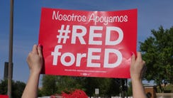 A teacher waves a #RedforEd sign at passing vehicles