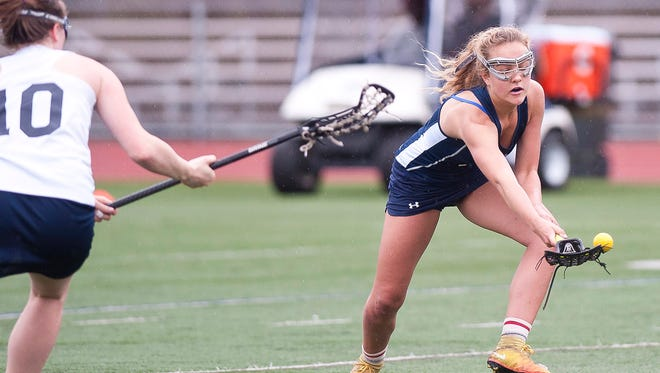 Mount Mansfield's Allison Charland, right, attempts to scoop up a ground ball during Tuesday's high school girls lacrosse game at Buck Hard Field.