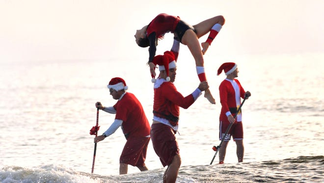Ed and Kymmie Martinez of Cocoa Beach, Fla., do some tandem sufing Dec. 24, 2017, surfing past two of the hundreds of Surfing Santas that had gathered at Cocoa Beach for the ninth year..