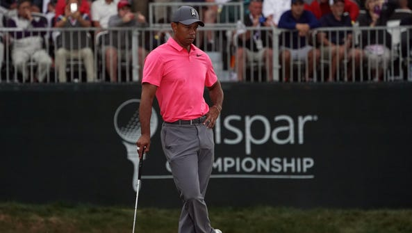 Tiger Woods stands on the 18th green during the third