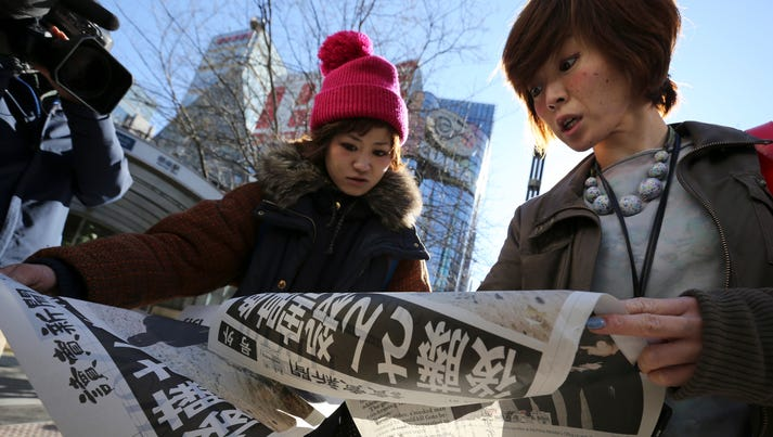 Women react as they read newspapers in Tokyo reporting