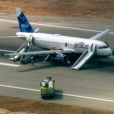 This still frame from video provided by KABC-TV, Los Angeles, shows a JetBlue airliner on the Long Beach Airport runway with emergency slides deployed Sept. 18, 2014.