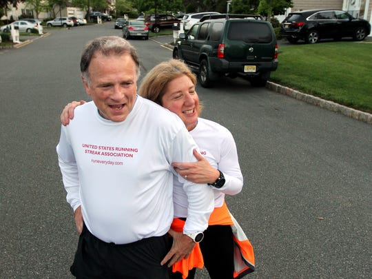 Mark Washburne gets a hug from his wife Diane, after finishing up a 3 mile run Wednesday morning, recording his 10,000 consecutive day of running, a streak that started 12/31/1989. Washburne currently has the 71st longest running streak in the nation, Diane, also a streaker, tallied her 1519 consecutive run today. May 17, 2017, Mendham, NJ.