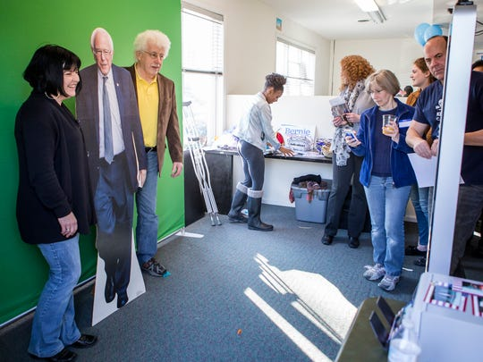 Rep. Kim Williams and Rep. John Kowalko pose with a cardboard cutout of the Bernie Sanders against a green screen at his Delaware campaign headquarters on Sunday afternoon.