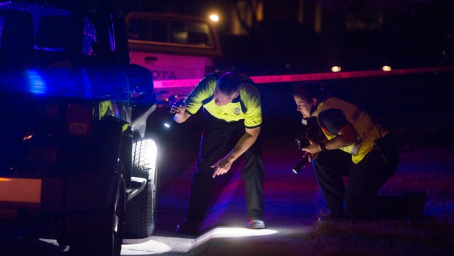 Investigators take photos of a Jeep parked in the 100 block of Yale Avenue suspected to be involved in a hit-and-run that occurred on two pedestrians near East Drake Road and Harvard Street Wednesday, July 13, 2016.