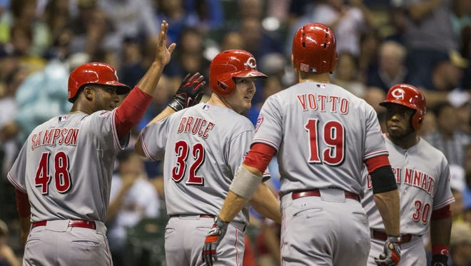 Cincinnati Reds' Jay Bruce (32) is greeted by teammates Joey Votto (19) and Keyvius Sampson (48) at home after hitting a three-run home run off Milwaukee Brewers' Matt Garza.