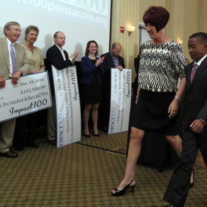 Paula Shell and Little Brother Jayden representing Big Brother Big Sisters step forward to receive one of the ten grants for their organization being offered by the Pensacola Bay Area Impact 100 Sunday afternoon during their annual meeting at the Hilton Pensacola Beach Gulf Front Conference Center.