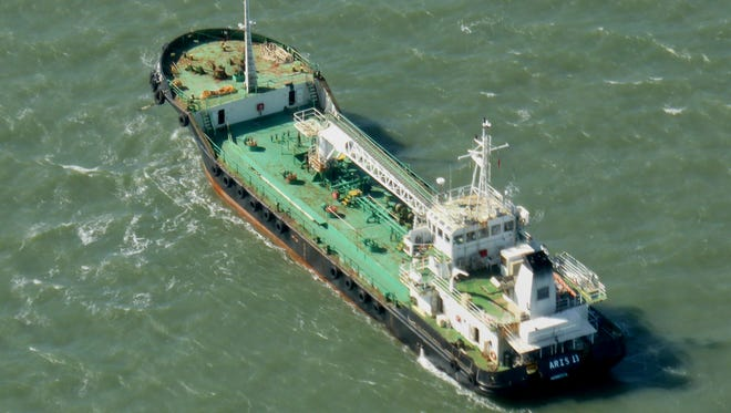 In this photo taken Monday, Oct. 27, 2014, the Aris 13 oil tanker is seen from a helicopter in the harbor of Gladstone, Australia.