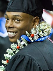 TeAndre Carter, who earned his associate of applied science in creative media technology, looks back and smiles while wearing a lei made of money on Thursday May 12, 2016 during the Doña Ana Community College Commencement at the Pan American Center.