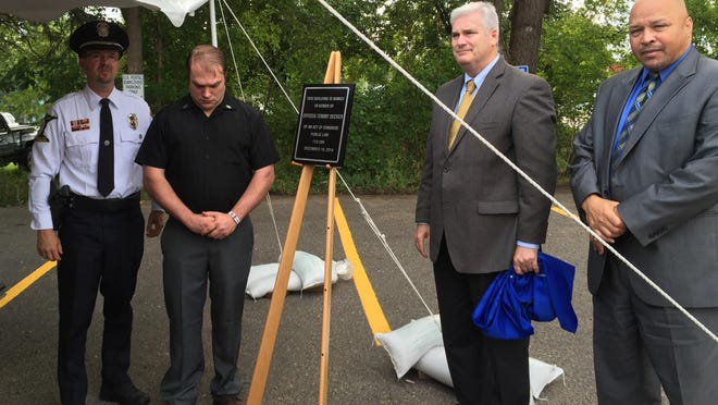 Cold Spring Police Chief Chris Boucher, far left, Joseph Decker, Congressman Tom Emmer, and U.S. Postal Department Northland District Manager Anthony Williams officially dedicate the renamed post office in Cold Spring in honor of slain police Officer Tom Decker.
